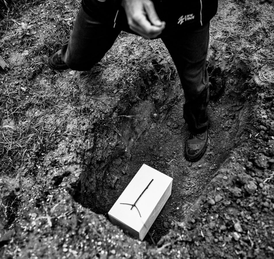A coffin containing a fetus placed in a pit inside the municipal cemetery, during the burial. The employs of cemetery services will proceed to cover the pit and place a cross.